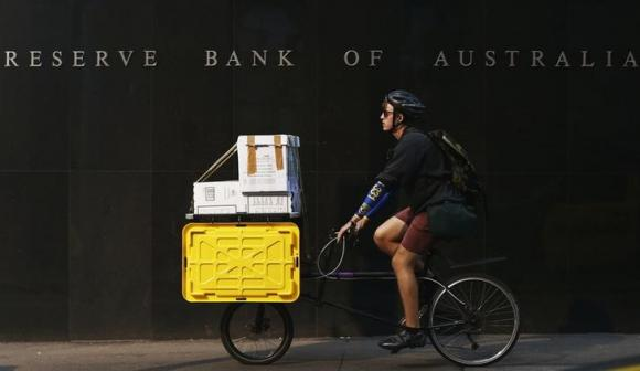 A worker on his bike rides past the RBA building in central Sydney